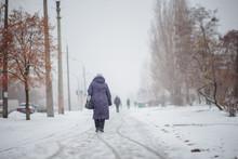 Elderly Woman In Dark Coat Wal...