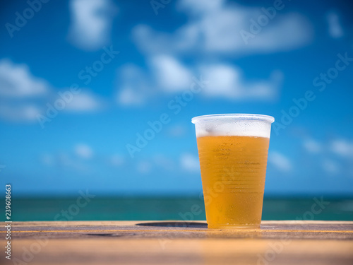 Foto op Canvas Bier / Cider Beer in plastic cup on wooden table over caribbean sea background