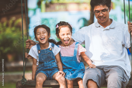 Leinwand Poster  Asian father and daughter having fun to ride on swings together in playground at