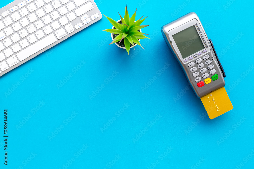 Fototapeta Electronic payments, online payments concept. Bank card inserted to payment terminal near computer keyboard on blue background top view space for text