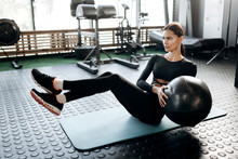 Slim Dark-haired Girl Dressed In Black Sports Clothes Doing Exercises For The Press On The Mat For Fitness With Fitness Ball In The Gym