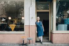 Portrait Of Confident Female Upholstery Worker Standing At Workshop Entrance