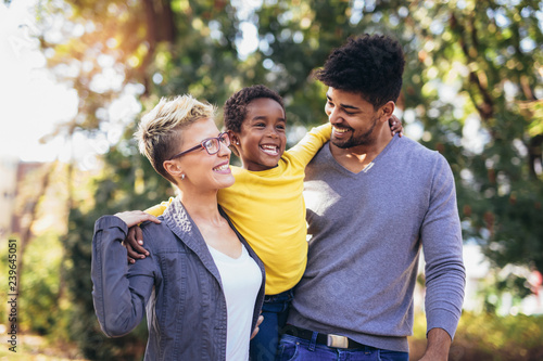 Fototapeta Happy young mixed race couple spending time with their daughter having fun obraz