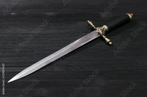 Dagger knife isolated on the black wooden background. Fototapeta