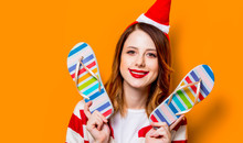 Portrait Of Young Redhead Woman In Santa Claus Hat And Striped Shirt With Colored Flip Flops On Yellow Background. Christmas Time