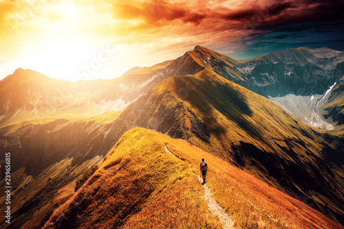 Photo Hiker following the trail on top of mountain range