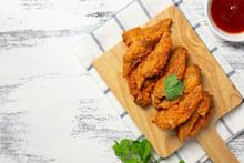 Fried Chicken Wings On A Wooden Board.