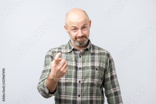 Photo  Playful bearded adult showing come here gesture with index finger and smiling over gray background