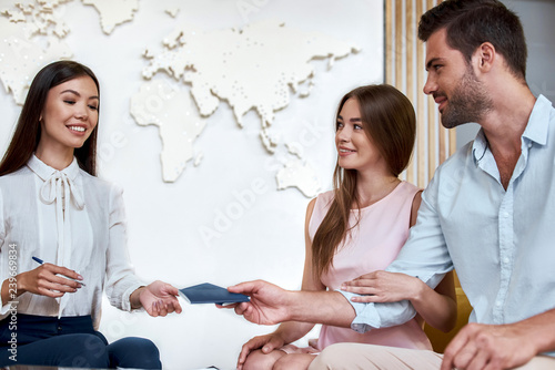 Young woman smiling and giving tickets, passport with visa to tourists Tablou Canvas