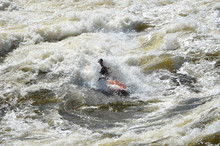 Kayaking In Very Rough Rapids. The River Is Violent With A Lot Of Turbulent Waves And Spray. The Face Of The Person In The Kayak Is Not Identifiable Do To The Spray And Because He Is In Shadow.