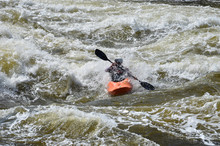 Kayaking In Very Rough Rapids. The River Is Violent With A Lot Of Turbulent Waves And Spray. The Face Of The Person In The Kayak Is Not Identifiable Due To The Spray In Front Of Him.