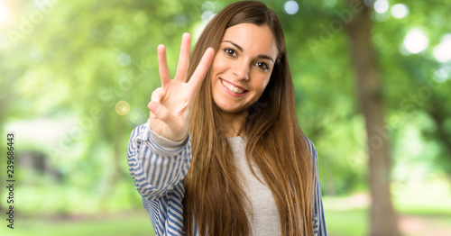 Fotografia  Young girl with striped shirt happy and counting three with fingers at outdoors