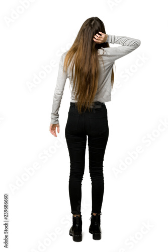Full-length shot of young girl on back position looking back while scratching head on isolated white background Wall mural