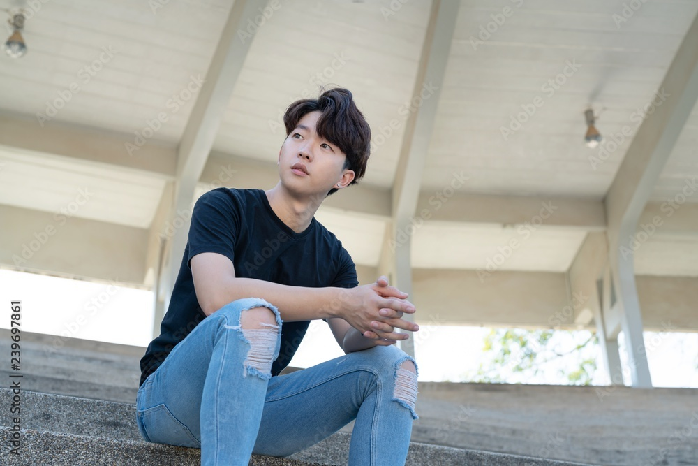 Fototapeta Handsome asian CASUAL man sit on a staircase posing on grandstand background.