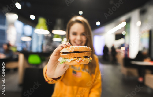 Fotografie, Obraz  Smiling girl sits at the table in a fast food restaurant and shows an appetizing big burger to the camera