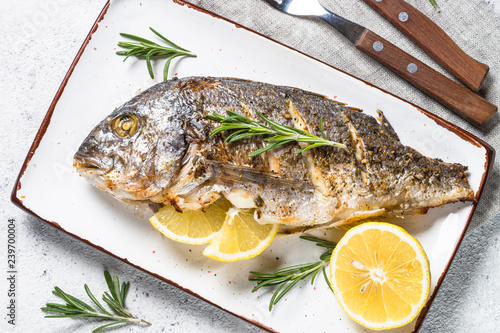 Fototapeta  Baked dorado fish with lemon and rosemary top view.