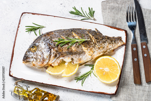Fotografie, Obraz  Baked dorado fish with lemon and rosemary top view.