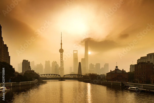 Foto auf Leinwand Shanghai Shanghai Financial Center and modern skyscraper city in misty gold lighting sunrise behind pollution haze, view from the bund in Shanghai, China. vintage picture style
