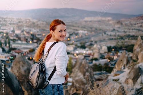 happy woman tourist is standing against mountain landscape