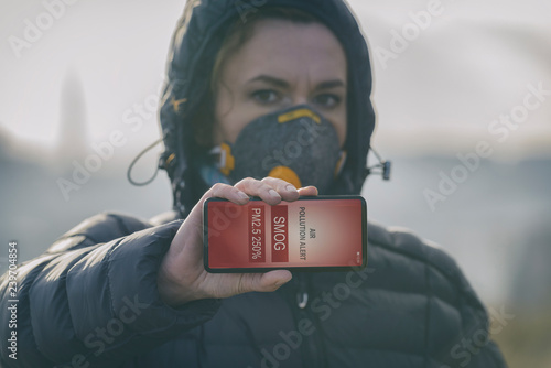 Obraz na plátně Woman wearing a real anti-smog face mask and checking current air pollution with