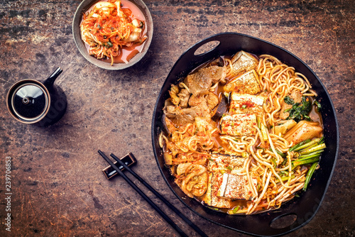 Traditional Korean kimchi jjigae with grilled pork belly and ramen as top view in a modern design Japanese cast-iron roasting dish - vintage