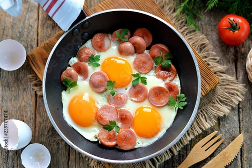 Homemade fried eggs with sausages in a frying pan on wooden background. Classic breakfast. Top view.