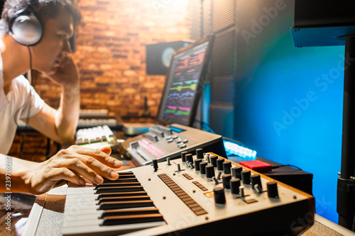Fotomural asian male composer playing midi keyboard synthesizer for making music in sound