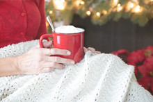 Christmas Photograph Of A Woman's Hands Holding A Bright Red Mug Of Hot Chocolate While She Relaxes Under A Knitted Afghan Throw With Christmas Lights And Red Poinsettia
