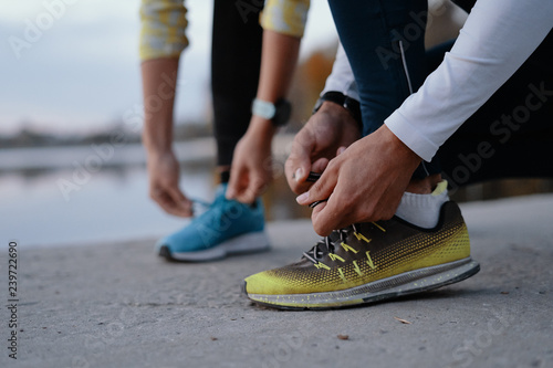 Pinturas sobre lienzo  Young couple yying sports shoes.