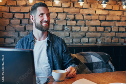 Young man drinking coffee in city cafe during lunch time and working on laptop