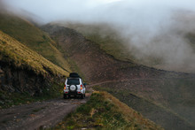 Silver Off-road Car On Road Trip In Mountains. Compact SUV Goes Uphill On Narrow Dangerous Road At Steep Mountainside In The Fog. Caucasus Mountains