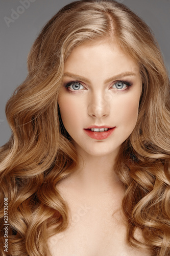 Fotografie, Obraz  Studio fashion portrait of attractive sensual young woman with long wavy fair hair and blue eyes looking at camera