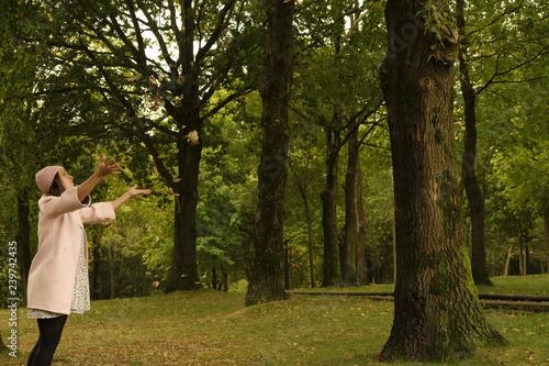 Plakat Kobieta rzuca suchymi liśćmi
