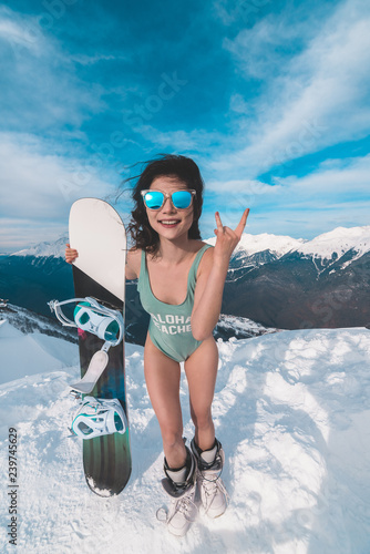 Attractive woman dressed in swimsuit with snowboard Canvas Print