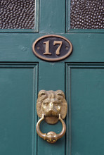 The House Number 17 On A Green Painted Door Frame In Hertfordshire, With A Brass Lion Door Knocker