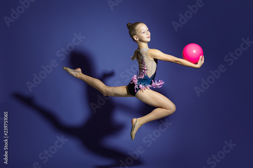 Foto auf AluDibond Gymnastik girl gymnast performs a jump with the ball. Frozen motion. Violet background. A child in a bathing suit for rhythmic gymnastics.