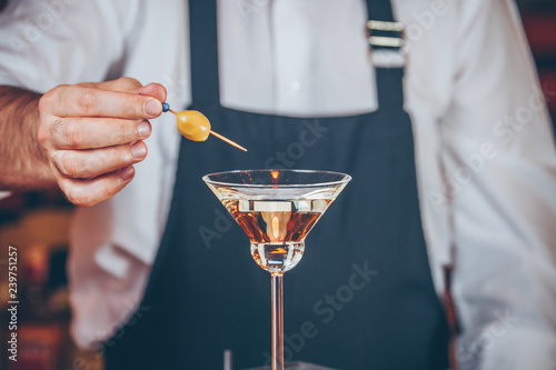 Poster Alcohol Barman decorating cocktail at a nightclub. Nightlife and entertainment concept