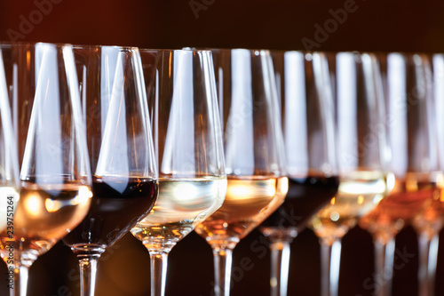 Papiers peints Vin Wine glasses in a row. Buffet table celebration of wine tasting. Nightlife, celebration and entertainment concept