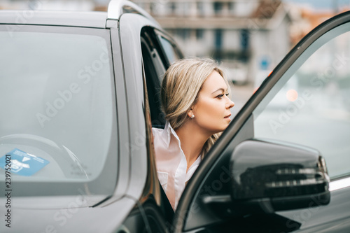 Beautiful woman coming out of the car Fototapet