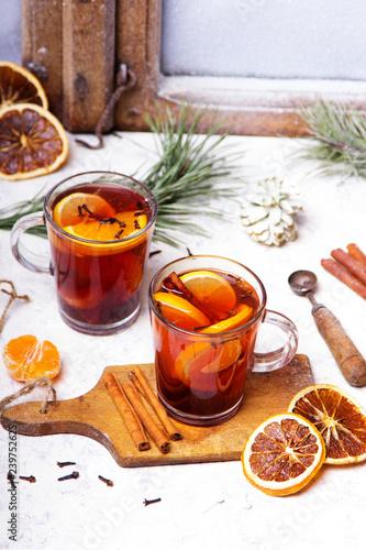 Fototapeta Świąteczny grzaniec z pomarańczami, cynamonem, anyżem i goździkami. Grzane wino na Boże Narodzenie,  obraz