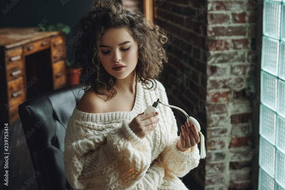 Fototapety, obrazy: Portrait of young beautiful confident woman using, holding luxury perfume in vintage white glass bottle with pump. Model wearing warm winter knitted sweater. Copy, empty space for text