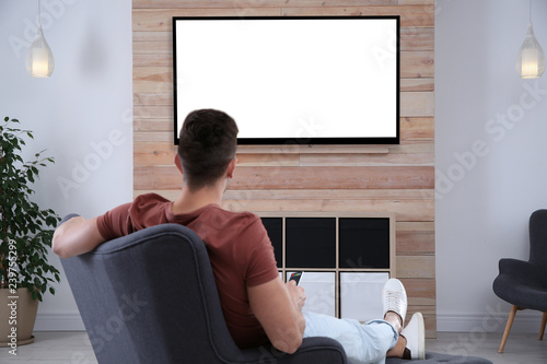 Young man watching TV in armchair at home. Mockup for design