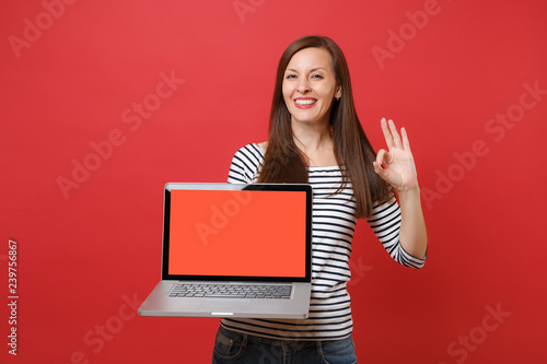 Fotografie, Obraz  Joyful young woman showing OK sign, holding laptop pc computer with blank black empty screen isolated on bright red wall background
