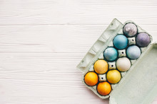 Stylish Easter Eggs In Carton Tray On White Wooden Background, Top View. Modern Colorful Easter Eggs Painted With Natural Dye In Different Colors. Happy Easter, Eco Concept. Space For Text