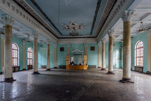 Interior of large column hall with fretwork at abandoned mansion