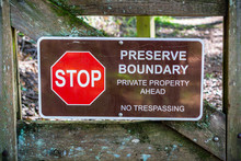 """""""Stop; Preserve Boundary; Private Boundary Ahead; No Trespassing"""" Sign Posted On A Wooden Gate"""