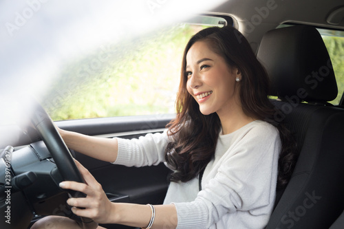 Vászonkép Asian women driving a car and smile happily with glad positive expression during