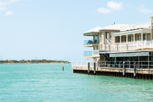 Yellow White Wooden Beach House, Rental Home, Property By Ocean Sea View With Green Blue Water, Sky By Jetty, Pier, Marina, Wharf In Florida Island Keys City