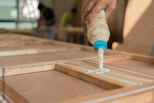 Obraz wood work carpenter concept with close up hand use glue for work - fototapety do salonu