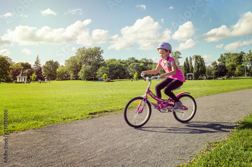 Fotografie, Obraz  Girl in a helmet riding a bicycle. Cyclist in summer park.